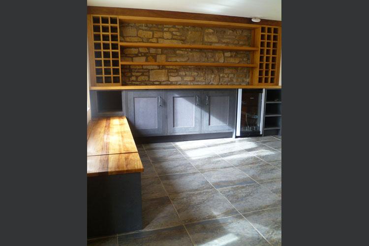 Bespoke drinks area with Iroko wine racks and window seat